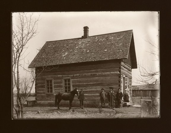 Hewn wood cabin with people & horse